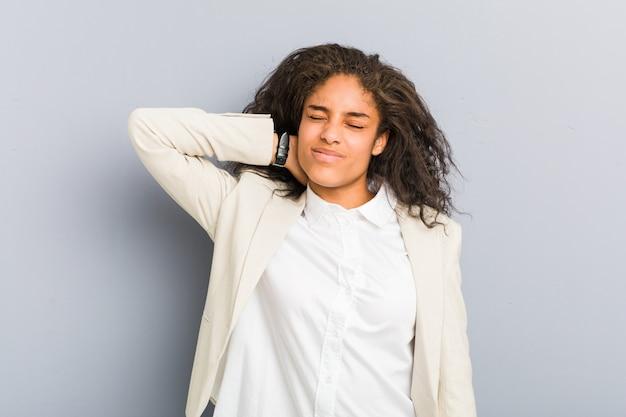 Молодая афро-американская бизнес-леди страдая боль в шее из-за сидячего образа жизни.