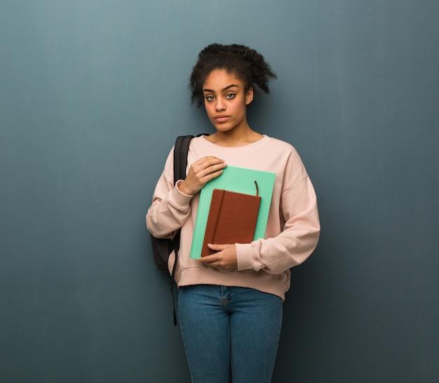まっすぐ見ている若い学生黒人女性。彼女は本を持っています。