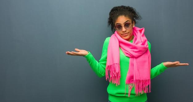 Молодая афро-американская девушка с голубыми глазами сомневаясь и пожимая плечами