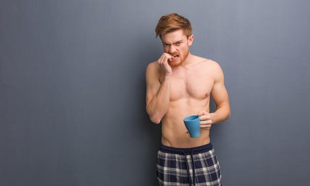 若い上半身裸の赤毛の男が爪をかむ、神経質で非常に心配しています。彼はコーヒーマグを持っています。