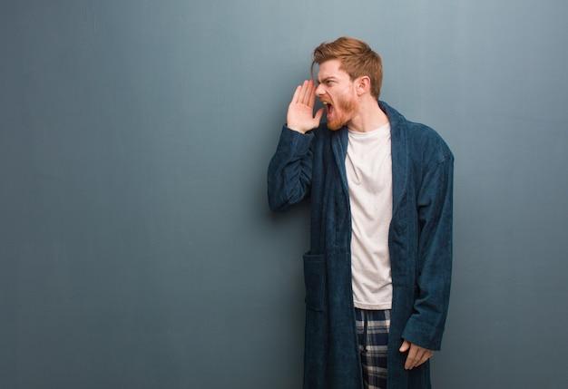 Молодой рыжий мужчина в пижаме шепчет сплетни подтекст
