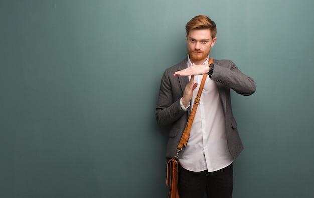 タイムアウトジェスチャーを行う若い赤毛ビジネス男