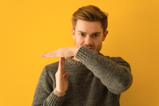 Молодой рыжий мужчина лицо крупным планом делает жест тайм-аут