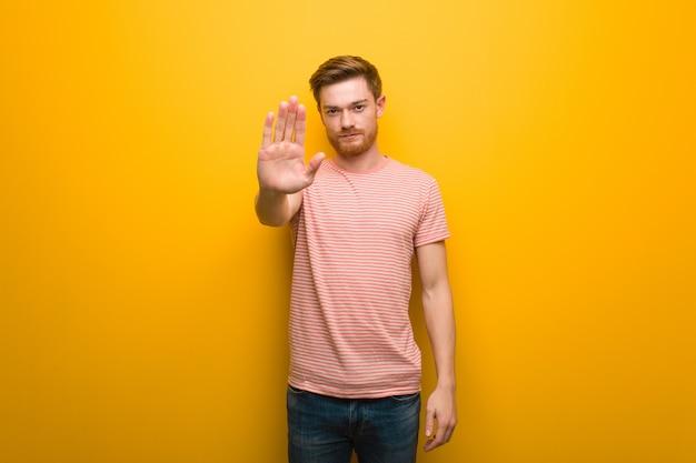 前に手を置く若い赤毛の男