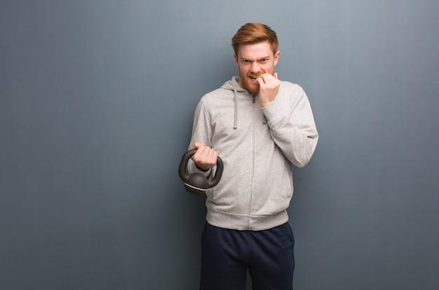 爪をかむ若い赤毛フィットネス男、神経質で非常に心配しています。ダンベルを保持しています。