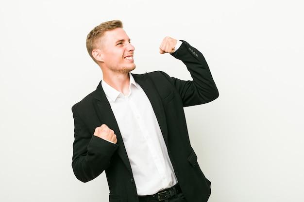勝利、勝者の概念の後拳を上げる若い白人ビジネスマン。