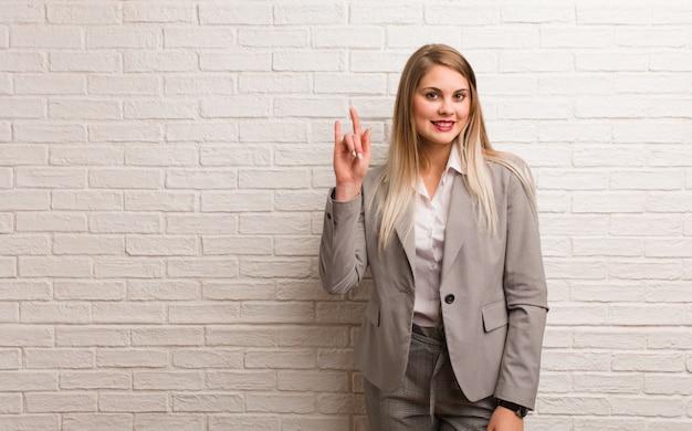 ロックジェスチャーを行う若いロシアビジネス女性