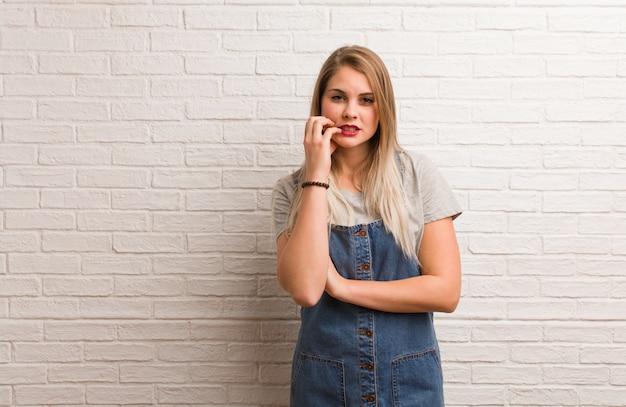 若いロシアの流行に敏感な女性の爪をかむ、神経質で非常に不安