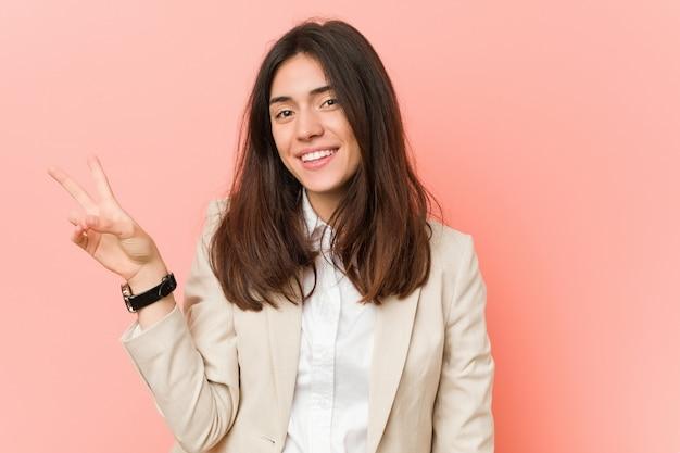 指で平和のシンボルを示すうれしそうな屈託のないピンクに対して若いブルネットビジネス女性。