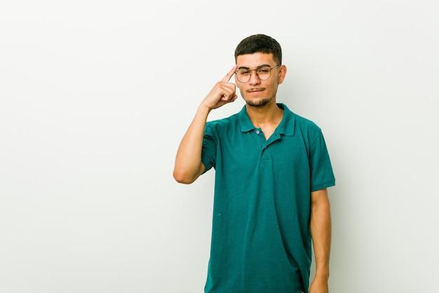 ヒスパニック系の若者が指で寺院を指して、考えて、タスクに焦点を当てた。