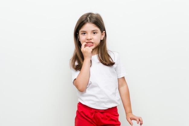 Маленькая кавказская девушка кусает ногти, нервная и очень взволнованная.