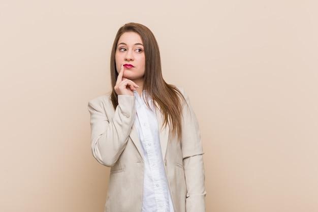 疑わしいと懐疑的な表情で横に探している若いビジネス女性。
