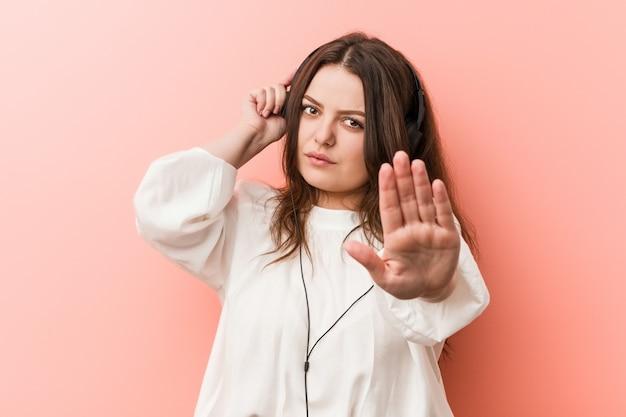 伸ばした手があなたを防止し、一時停止の標識を示すと立ってヘッドフォンで音楽を聴く若いプラスサイズ曲線美の女性。