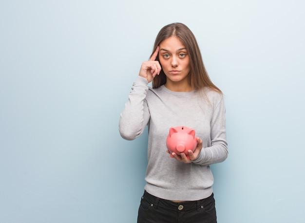 アイデアを考えて若いかなり白人女性。彼女は貯金箱を持っています。