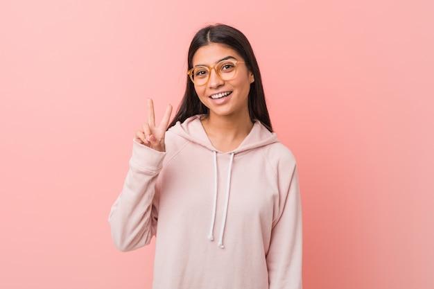 勝利のサインを示し、広く笑顔のカジュアルなスポーツの外観を身に着けている若いかなりアラブの女性。