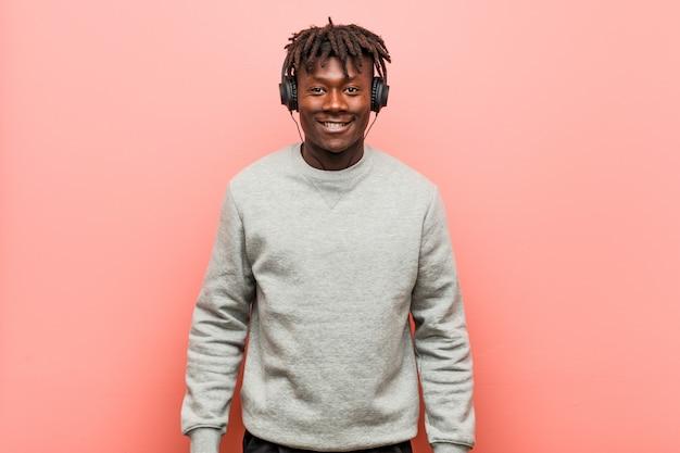 幸せ、笑顔、陽気なヘッドフォンで音楽を聴く若いラスタ黒人男性。