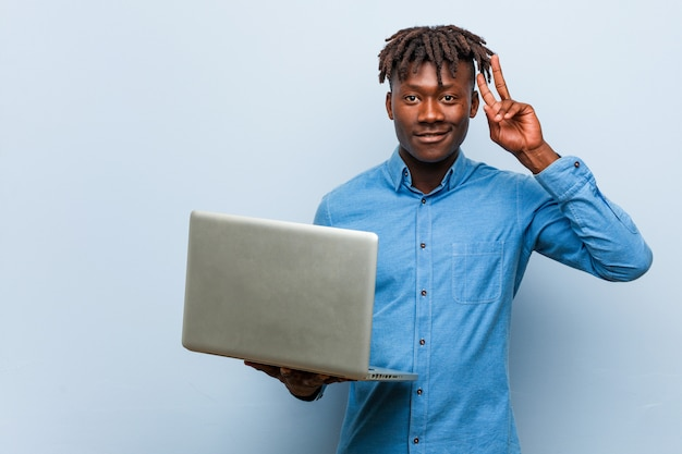 Молодой раста черный человек держит ноутбук, показывая знак победы и широко улыбаясь.