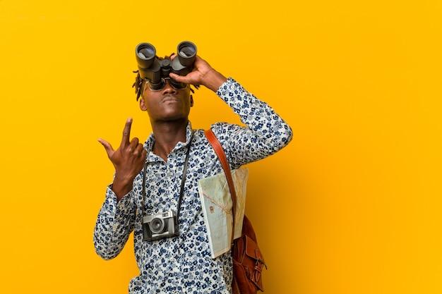 Молодой африканский туристский человек стоя против желтого цвета держащ бинокль
