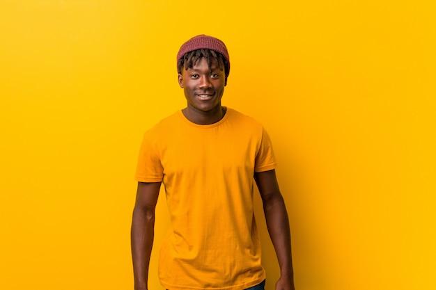 帽子をかぶって黄色に対して立っている若いアフリカ系アメリカ人のトレンディな男