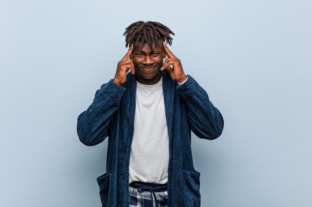 Пижама молодого африканского чернокожего человека нося сфокусировала на задаче, держа его указательные пальцы указывая голова.