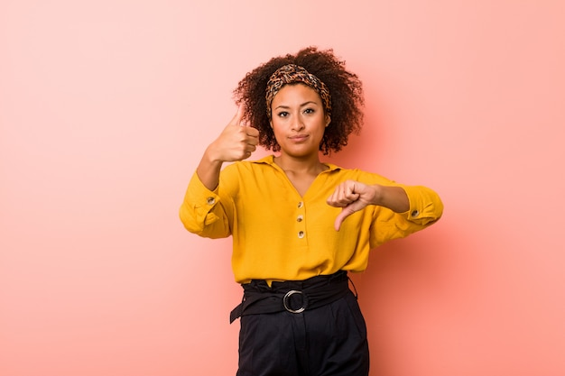 Молодая афро-американская женщина против пинка показывая большие пальцы руки вверх и большие пальцы руки вниз, трудно выбрать