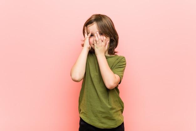 おびえた、緊張した指の間で小さな男の子が瞬きます。