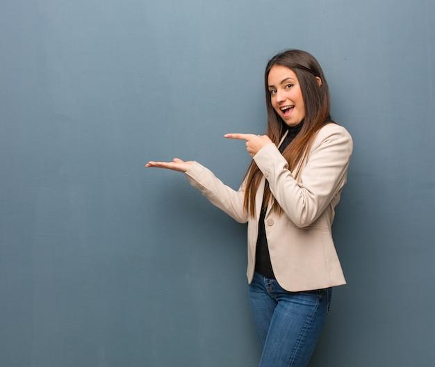 Молодая бизнес-леди держа что-то с рукой