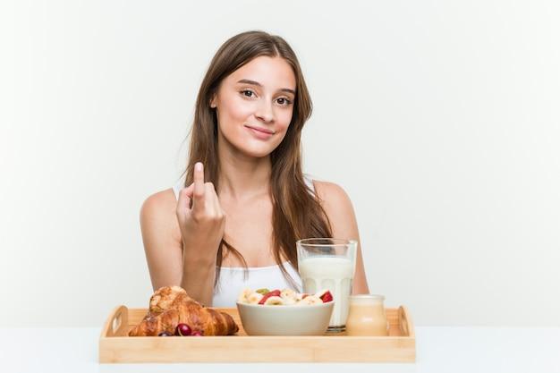 Молодая женщина с завтрака, указывая пальцем на вас, как будто приглашая подойти