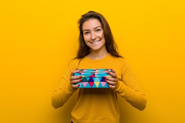 幸せ、笑顔、陽気な贈り物を保持している若いヨーロッパの女性