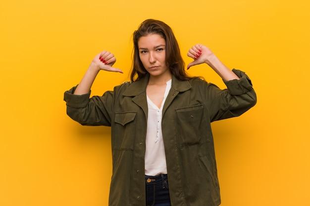 黄色の背景に分離された若いヨーロッパの女性は誇りに思って、自信を持って、次の例