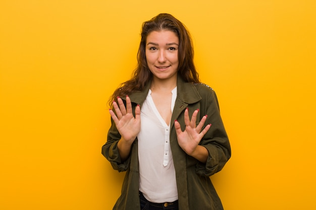 嫌悪のジェスチャーを示す誰かを拒否する黄色の背景に分離された若いヨーロッパの女性