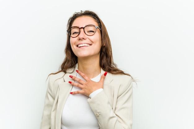 Молодая европейская деловая женщина громко смеется, держа руку на груди