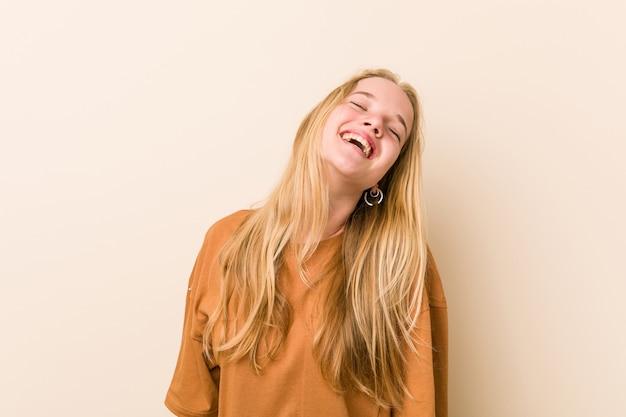 Симпатичный и естественный подросток женщина спокойно и счастливо смеется, шея растянута, показывая зубы.