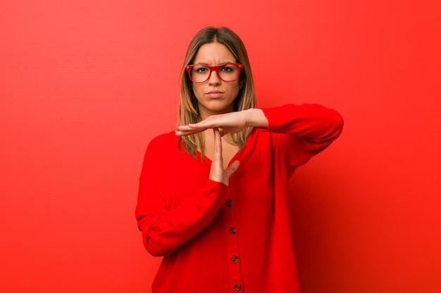 タイムアウトジェスチャーを示す壁に若い本物のカリスマ的な実在の女性。