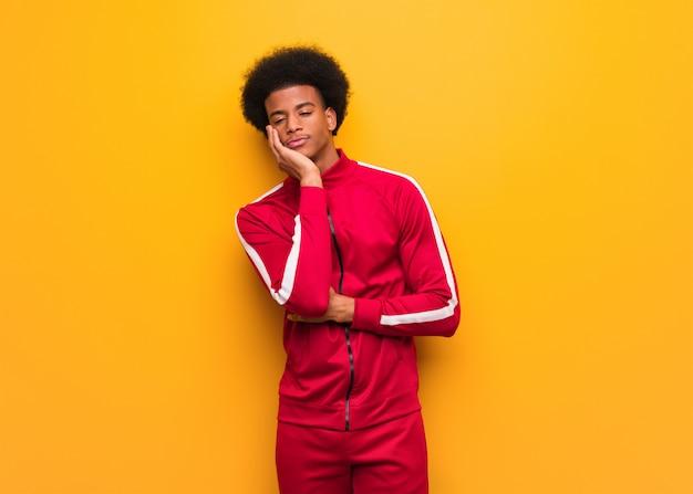 Молодой спортивный черный человек за оранжевой стеной устал и очень сонный