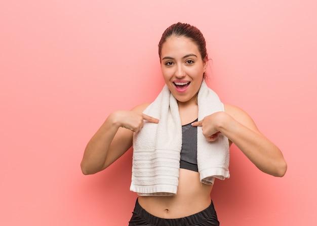 Молодая фитнес женщина удивлена, чувствует себя успешной и процветающей