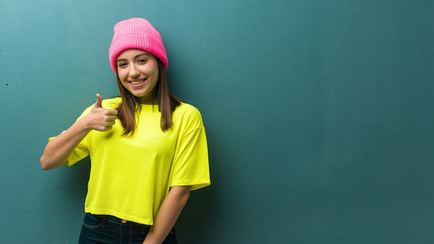 若い現代女性の笑顔と親指を上げる