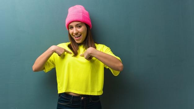 Молодая современная женщина удивлена, чувствует себя успешной и процветающей