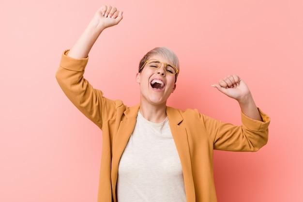 特別な日を祝うカジュアルなビジネス服を着ている若い白人女性がジャンプし、エネルギーで腕を上げます。