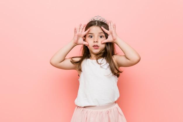 成功の機会を見つけるために目を開いたままのプリンセスルックを着た少女