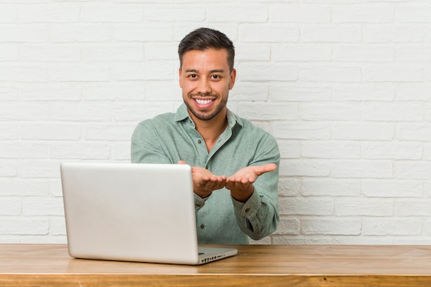 Молодой филиппинский человек, сидящий, работает со своим ноутбуком, держа что-то ладонями, предлагая камеру