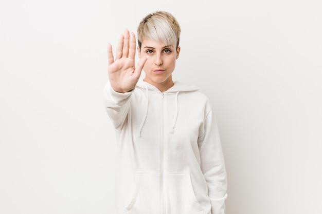 Молодая соблазнительная женщина, одетая белая толстовка стоя с протянутой рукой, показывая знак остановки, предотвращая вас.