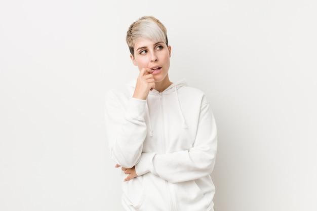 白いパーカーを身に着けている若い曲線の女性は、コピーを見て何かについてリラックスした思考。