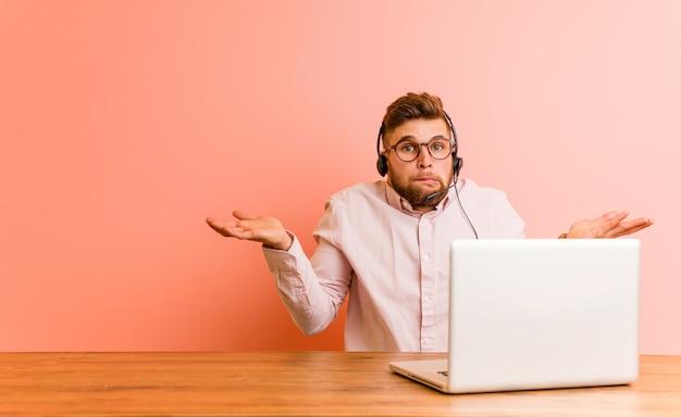 コールセンターで働いている若い男は混乱していて、コピーを保持するために彼の手を上げる疑わしいです。