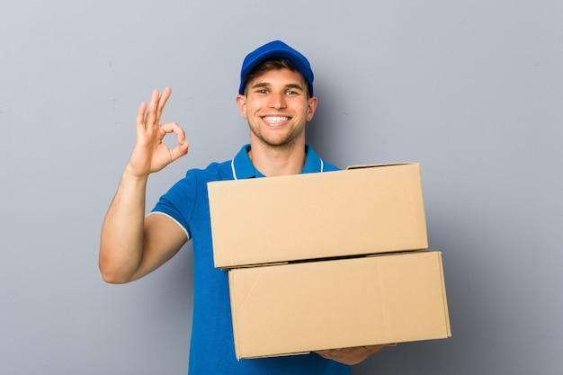 Молодой человек доставки пакетов веселый и уверенный, показывая ок жест.