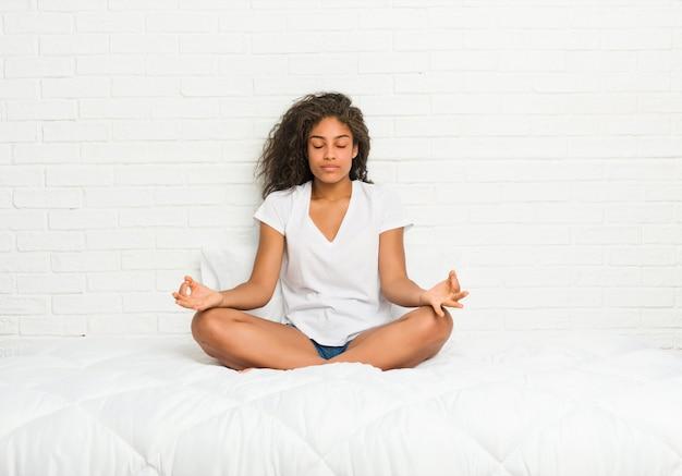 Молодая афро-американская женщина протягивая на кровати