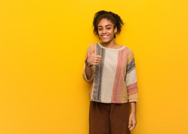 笑顔と親指を上げる青い目を持つ若い黒人アフリカ系アメリカ人の女の子