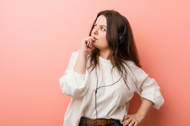 疑わしいと懐疑的な表情で横向きのヘッドフォンで音楽を聴く若いプラスのサイズの曲線の女性