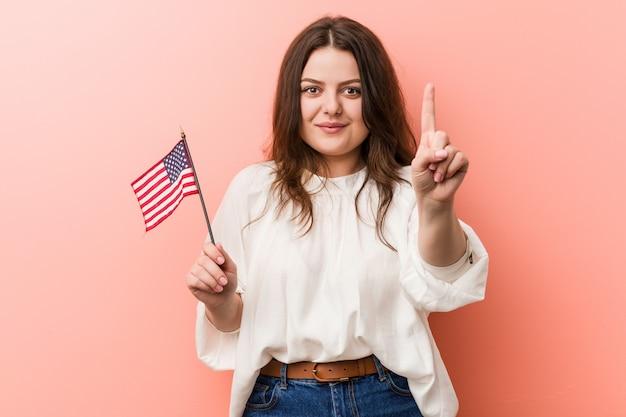 Молодые пышные плюс размер женщина держит флаг сша, показывая номер один с пальцем