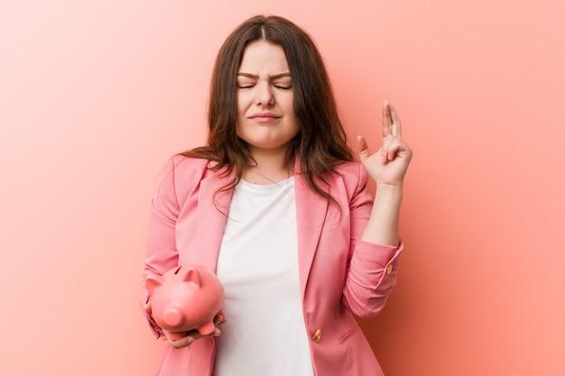幸運のために指を交差貯金を保持している若いプラスのサイズの曲線のビジネス女性